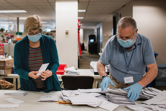 Andrea Lerner (left), and her husband, Ira Lerner, sift through the mail-in applications at the Voter Registration office in the Lehigh County Government Center in Allentown, Pa.