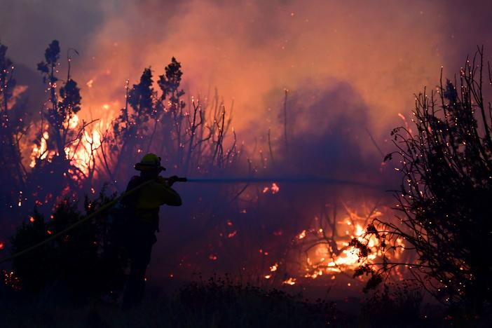 A firefighter works to put out flames of the Bobcat Fire in Juniper Hills, Calif. As of Sunday, the wildfire has grown to more than 99,000 acres and is 15% contained.