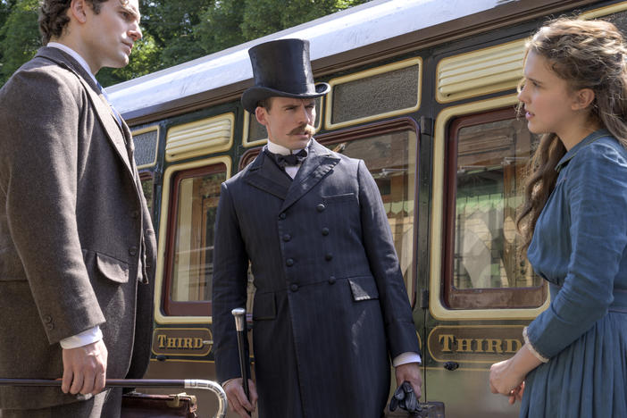 """The train's afoot!"": (L to R) Sherlock (Henry Cavill) and Mycroft (Sam Claflin) literally look down on their younger sister Enola (Millie Bobby Brown) in Netflix's <em>Enola Holmes.</em>"
