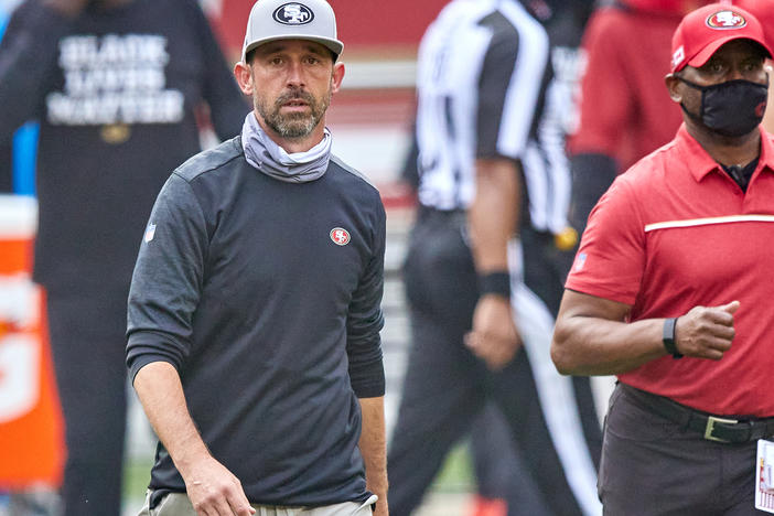 The NFL has fined San Francisco 49ers head coach Kyle Shanahan and two other coaches for not following rules about keeping their faces covered. Here, Shanahan walks off the field after his team's Sept. 13 game against the Arizona Cardinals.