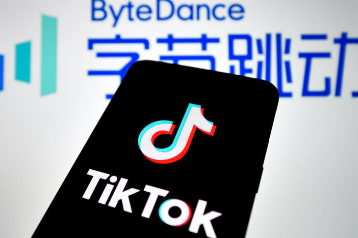 In this photo illustration, a TikTok logo seen displayed on a smartphone with a ByteDance logo picture in the background.