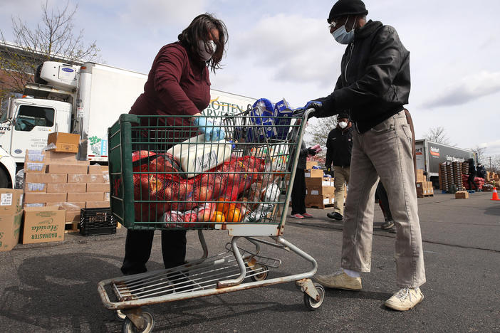A volunteer loads food into a cart at a mobile pantry in Detroit in April 2020. The COVID-19 pandemic has led to an uptick in the demand at food banks.