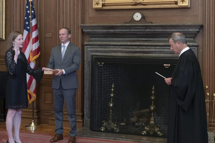 Chief Justice John Roberts Jr. administers the judicial oath to Judge Amy Coney Barrett at the Supreme Court on Tuesday. Barrett's husband, Jesse, holds the Bible.