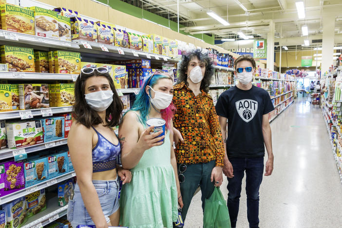Increasingly, many people in the U.S., like these teens in a Miami grocery story in August, now routinely wear face masks in public to help stop COVID-19's spread. But social distancing and other public health measures have been slower to catch on, especially among young adults, a national survey finds.