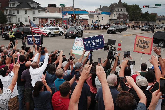 Trump supporters and Trump protesters watch a passing motorcade carrying the president last month in Kenosha, Wis.