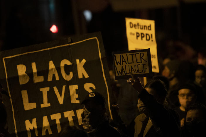 "Demonstrators hold placards reading ""BLACK LIVES MATTER,"" ""Walter Wallace JR."" and DEFUND PPD"" as they gather in protest near the location where Wallace, a 27-year-old Black man, was killed by two police officers in Philadelphia. Police officers said he was armed with a knife."