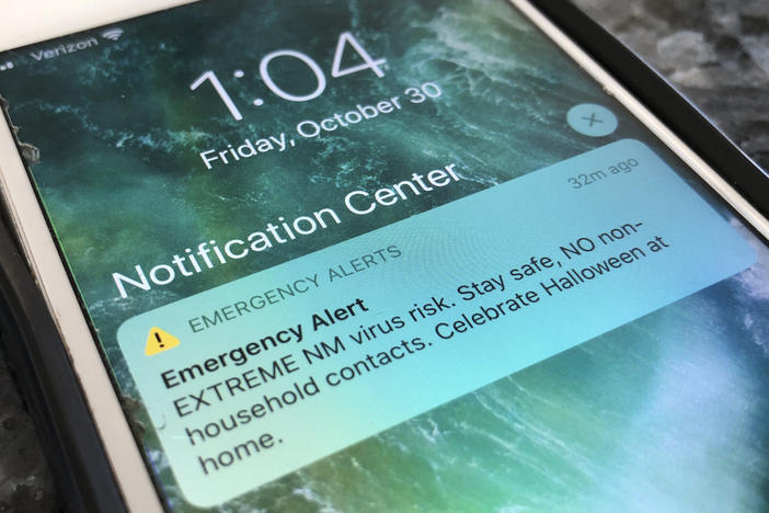 An emergency alert regarding the coronavirus pandemic is displayed on a cellphone Friday in Rio Rancho, N.M. The alert was sent out to New Mexicans across the state urging them to stay home amid a surge in COVID-19 cases and record-high hospitalizations.