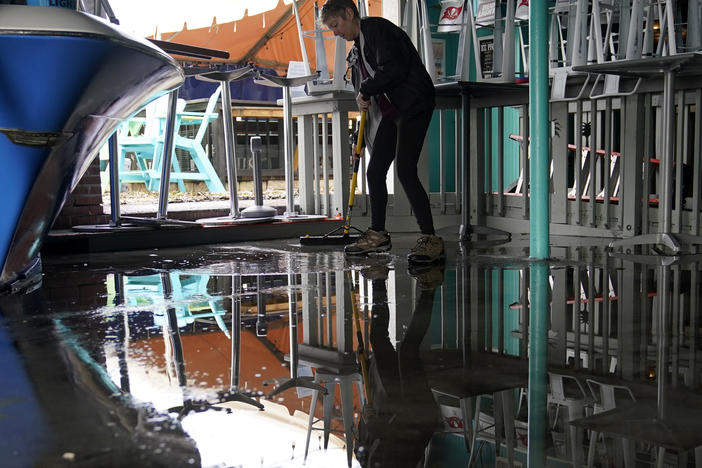 Kate Connell sweeps water and mud from the floor at Salty's Gulfport bar Thursday in Gulfport, Fla., in the aftermath of Tropical Storm Eta.