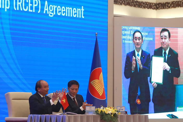 Vietnamese Prime Minister Nguyen Xuan Phuc (left) and Trade Minister Tran Tuan Anh applaud next to a screen showing Japanese Prime Minister Yoshihide Suga and Trade Minister Hiroshi Kajiyama holding up signed RCEP agreement, in Hanoi, Vietnam. China and 14 other countries have agreed to set up the trading bloc.