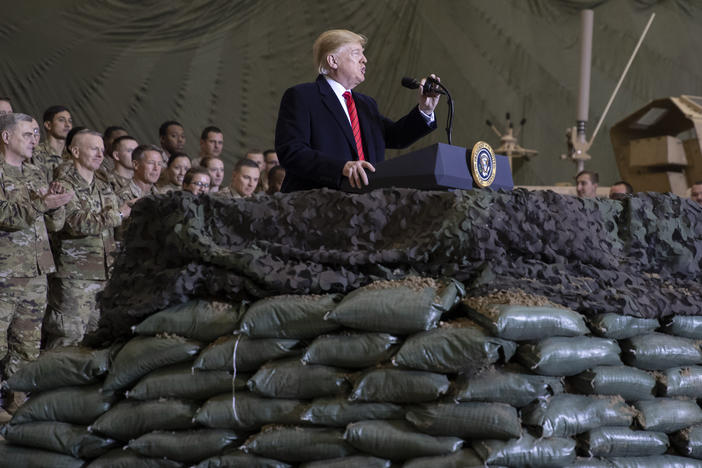 President Trump speaks to U.S. troops at Bagram Airfield, Afghanistan, on Thanksgiving Day 2019. The Trump administration says it's cutting U.S. forces from 4,500 to 2,500 troops in Afghanistan, one of several abrupt military moves announced recently.
