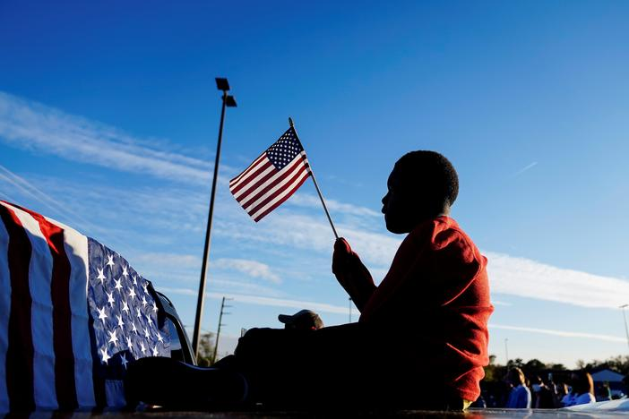 Xavier Watts, 9, waves an American flag during a campaign rally for Georgia Democratic U.S. Senate candidates Jon Ossoff and Raphael Warnock on Nov. 15 in Marietta, Ga.
