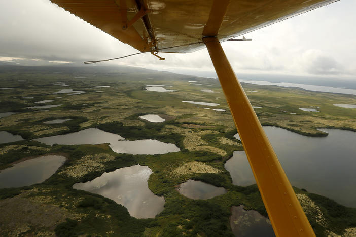 The view beneath the wing of a float plane as it flies over the wetlands, streams and lakes of Bristol Bay, Alaska.
