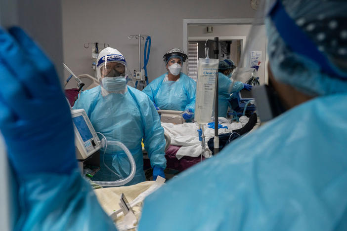 Medical staff prepare for an intubation procedure on a COVID-19 patient in a Houston intensive care unit. In some parts of the U.S., as hospitals get crowded, hospital leaders are worried they may need to implement crisis standards of care.