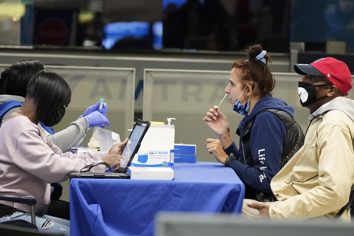 Travelers self-test for the coronavirus at a mobile testing site at New York City's Penn Station in the days leading up to Thanksgiving. The U.S. is currently seeing record hospitalizations for COVID-19, and health experts fear more surges are on their way.