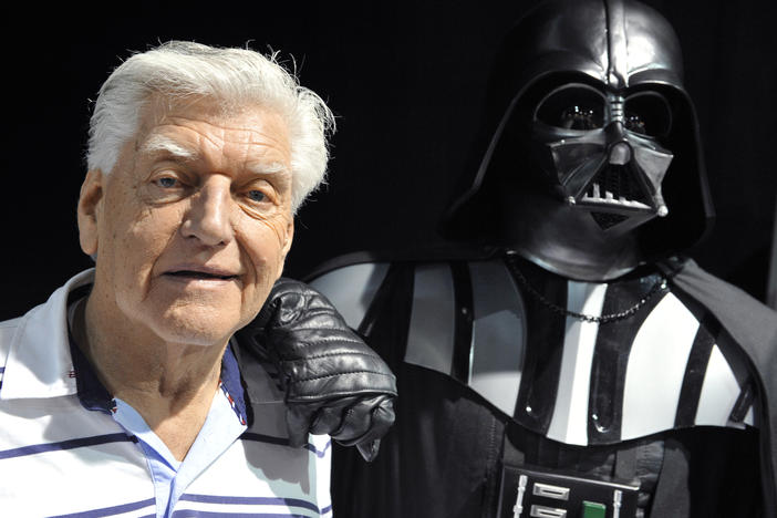 British actor David Prowse, who played Darth Vader in the first Star Wars trilogy, poses with a fan dressed in a Darth Vader costume during a Star Wars convention on April 27, 2013. On Sunday morning, Prowse's management company shared the news of his death at age 85.