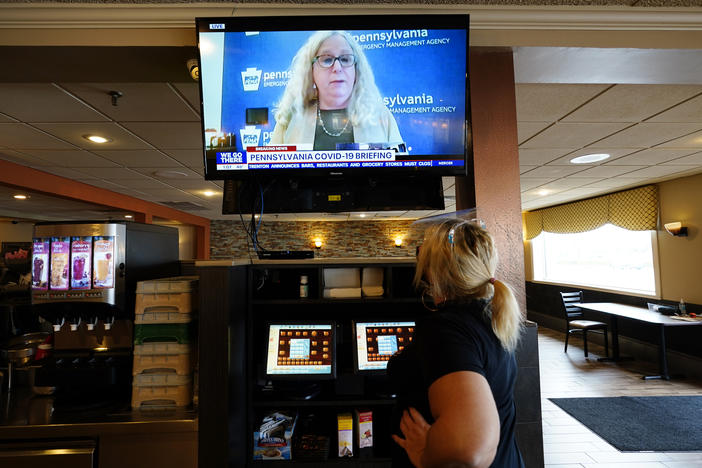 "A waitress in South Philadelphia watches a television briefing by Pennsylvania's health secretary, Dr. Rachel Levine, on Nov. 17. Levine says a COVID-19 vaccine is ""the light at the end of the tunnel,"" but says it will be months before it's available to the general public."