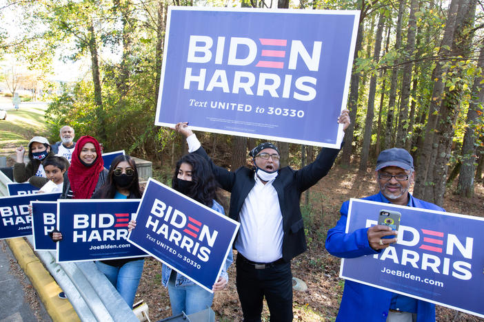 Voters wave Biden-Harris campaign signs at the entrance to a polling station in Gwinnett County, Ga., on Nov 3. Gwinnett is one of the five Atlanta metro counties that saw a dramatic increase in turnout among Asian American and Pacific Island voters this year.