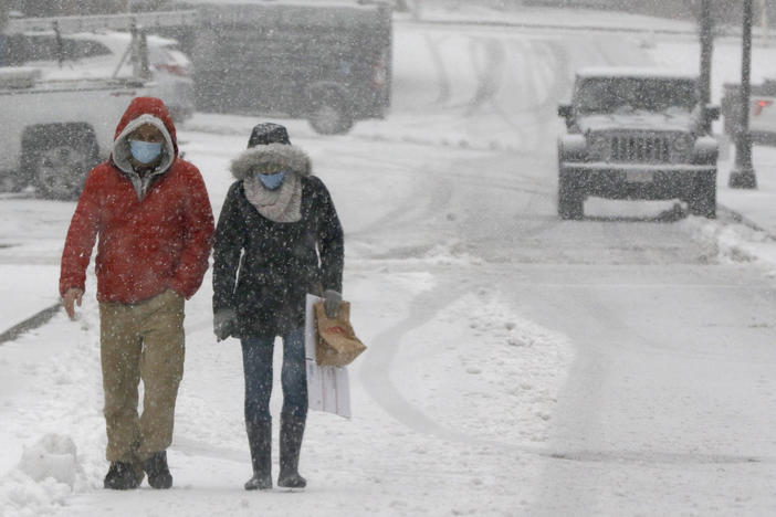 A couple walks through heavy snow on Saturday in downtown Marlborough, Mass. The northeastern United States is seeing the first big snowstorm of the season.