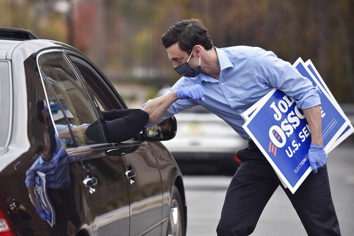 Jon Ossoff, a Georgia Democratic candidate for U.S. Senate, greets a supporter with an elbow bump at a drive-through event to pick up yard signs last month in Alpharetta, Ga. Ossoff is in a runoff with Republican David Perdue, the incumbent, for the U.S. Senate.