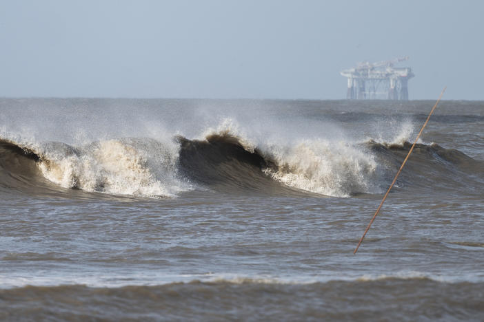 Hurricane Laura sends large waves crashing on a beach in Cameron, La., on Aug. 26 as an offshore oil rig appears in the distance. The most active hurricane season on record was just one of many challenges facing the oil industry this year — aside from the attention-grabbing crisis of the pandemic.