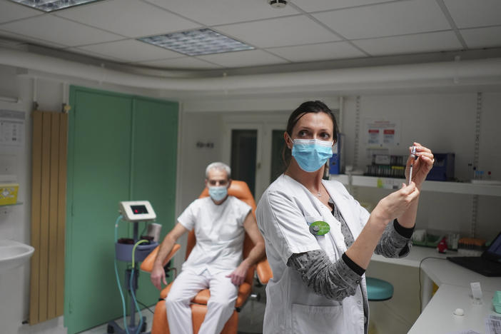 "A nurse prepares to administer the Pfizer-BioNTech COVID-19 vaccine to Dr. Jean-Christophe Richard in La Croix-Rousse hospital, in Lyon, France, on Wednesday. Amid public outcry, France's health minister promised Tuesday an ""exponential"" acceleration of his country's slow coronavirus vaccination process."
