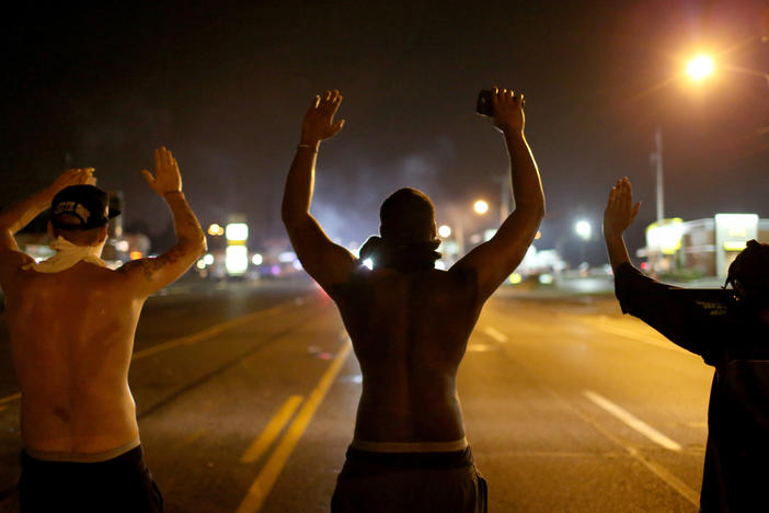 "Demonstrators raise their arms and chant, ""Hands up, don't shoot,"" in August 2014 as they protest the shooting death of Michael Brown in Ferguson, Mo."