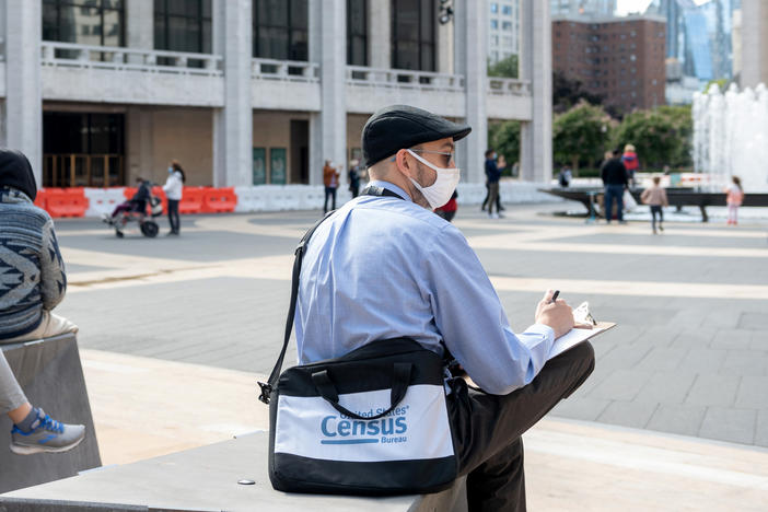 A U.S. census worker sits in the plaza of the Lincoln Center for the Performing Arts in New York City in September. The Census Bureau announced Wednesday that the first results of the 2020 census are expected to be released by April 30.