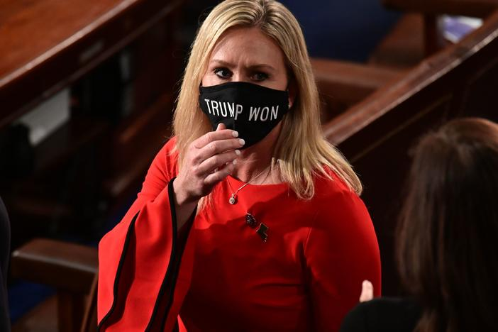 "Rep. Marjorie Taylor Greene, R-Ga., wears a ""Trump Won"" face mask as she arrives on the floor of the House to take her oath of office as a newly elected member of the House of Representatives on Jan. 3."