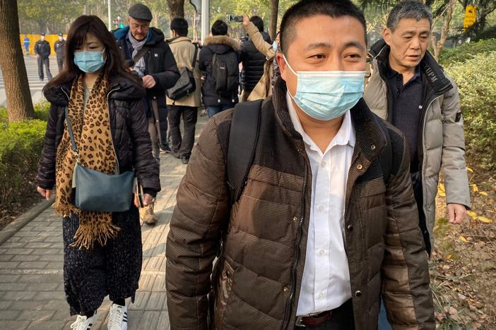 Lawyer Ren Quanniu (center), representing Chinese citizen journalist Zhang Zhan who reported on Wuhan's COVID-19 outbreak and was placed in detention since May, arrives at the Shanghai Pudong New District People's Court where Zhang is set for trial in Shanghai on Dec. 28. Ren has since been disbarred.