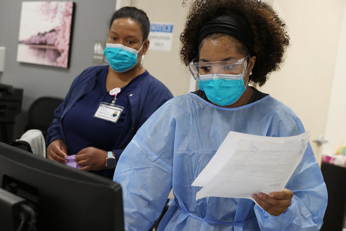 Workers at an urgent care facility in Woodbridge, Va., check health records while testing patients for COVID-19 on April 15, 2020.