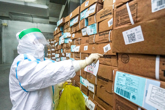 A health officer in a protective suit collects a sample from a package of imported frozen food for a coronavirus rapid test at a wholesale market in China.