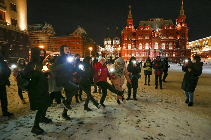 Young people dance shining their cellphone flashlights in support of jailed opposition leader Alexei Navalny and his wife Yulia Navalnaya near Red Square in Moscow on Sunday.