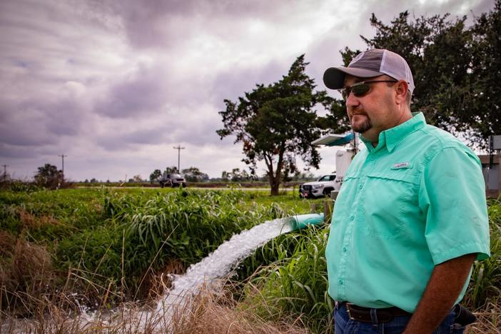 Christian Richard stands next to a groundwater well on his southwestern Louisiana farm. A centuries-old law allows landowners in the state to use as much water as they want for free.