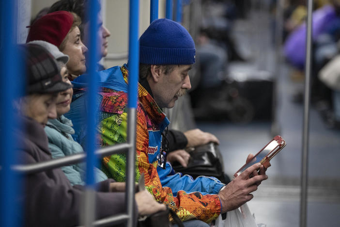 A man uses a tablet device in a subway train in Moscow in 2019. Russia's Internet regulatory agency announced it is slowing Twitter because the company has ignored requests to remove content harmful to children.