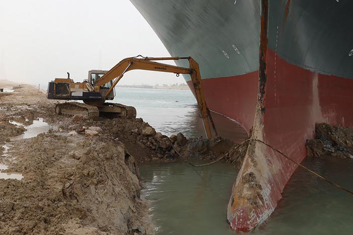 Heavy equipment is used to try to dig out the keel of the Ever Given, a massive cargo ship wedged across the Suez Canal.