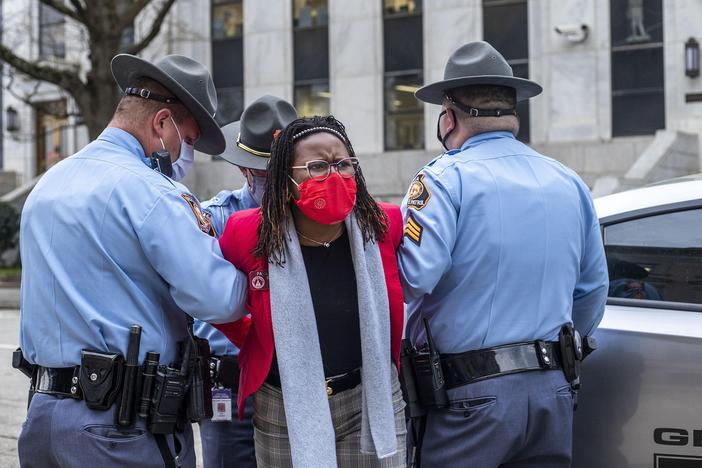 State Rep. Park Cannon is placed into the back of a Georgia State Capitol patrol car after being arrested at the state Capitol. Cannon was arrested after she attempted to knock on the door of Gov. Brian Kemp's office during his remarks after signing into law a sweeping Republican-sponsored overhaul of state elections.