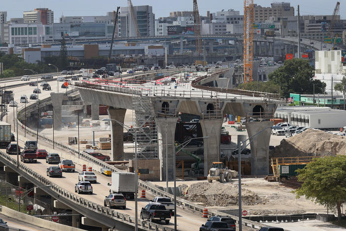 Workers improve a busy highway intersection in Miami. President Biden is proposing roughly $2 trillion to invest in the nation's infrastructure. His plan includes improvements for roads, bridges, transit, water systems, electric grids and Internet access.