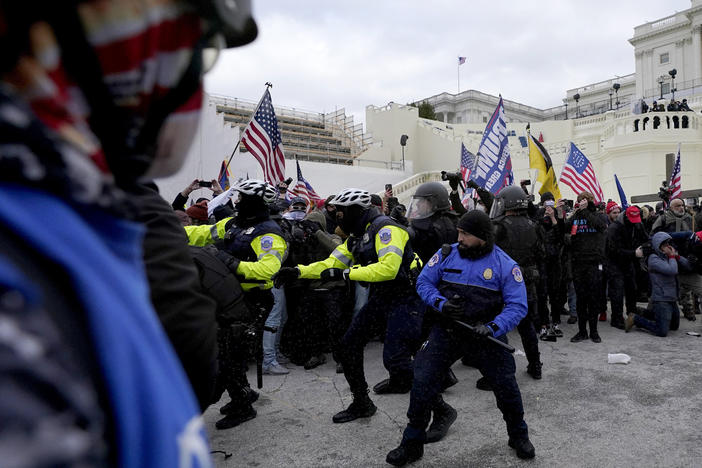 Police officers try to push back President Donald Trump supporters trying to break through a police barrier, Jan. 6 at the Capitol in Washington. Two U.S. Capitol police officers have sued Trump for allegedly inciting the mob that attacked them that day.