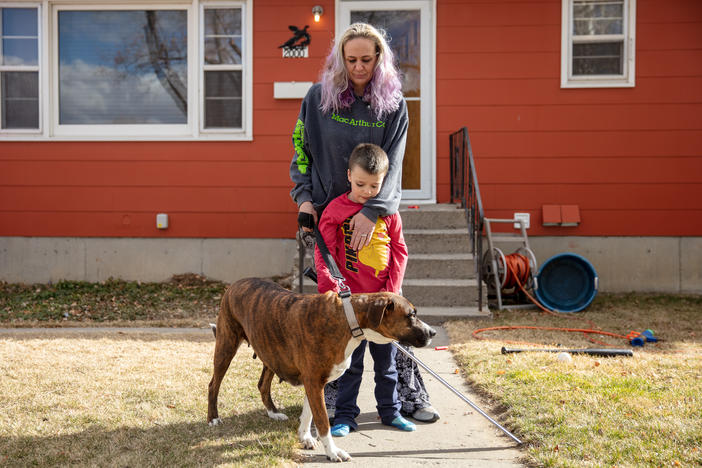 Barbara Gaught stands outside the home she's now renting in Billings, Mont., with her 5-year-old son, Blazen, and their dog, Arie. Gaught and her family were evicted from the mobile home they had owned outright and lived in for 16 years because they fell behind on 'lot rent' for the little plot of land under the mobile home.