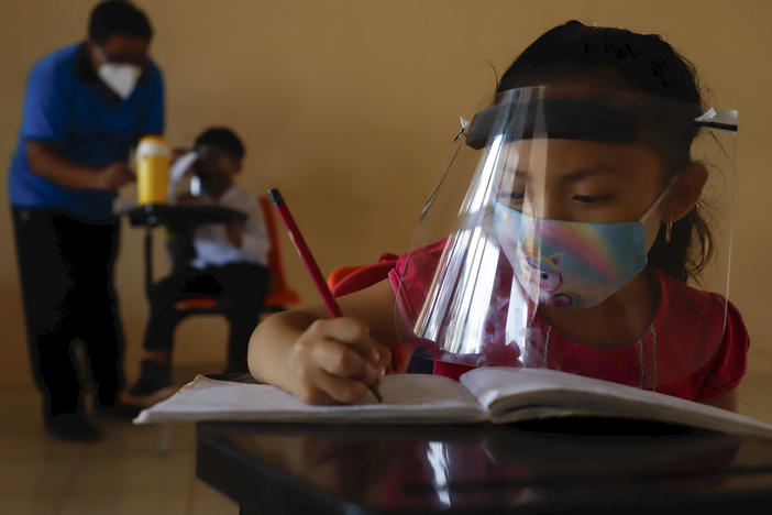 Wearing a mask and a face shield to curb the spread of the coronavirus, 10-year-old Jade Chan Puc writes in her workbook during the first day of class in Hecelchakán, Campeche state, Mexico, on April 19. On average, schools in Latin America and the Caribbean were closed longer than any in any other region, according to UNICEF.